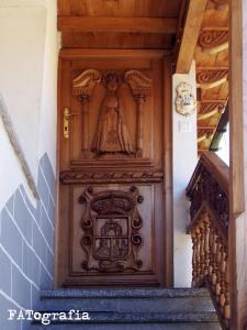Puerta principal vivienda. Virgen del Alba y escudo de Quirós